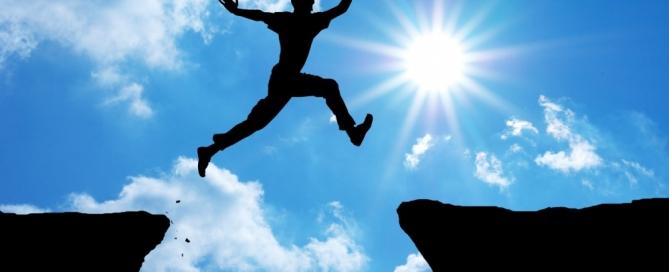 Man jumping over gap in rocks