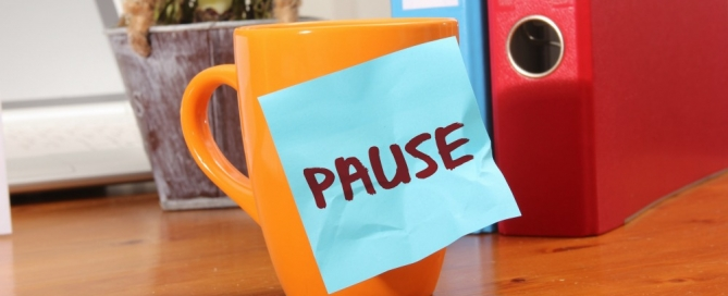 Mug with a sticky note that says Pause